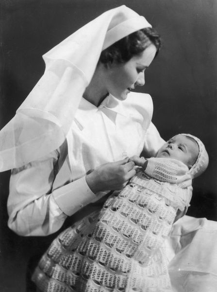 A nurse in white uniform holds a baby dressed in a long crocheted shawl and bonnet