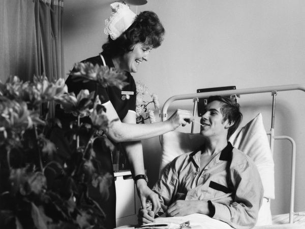 Scene at the Metropolitan Police Medical Centre, Hendon, north west London, with a nurse taking a patient's temperature with a thermometer