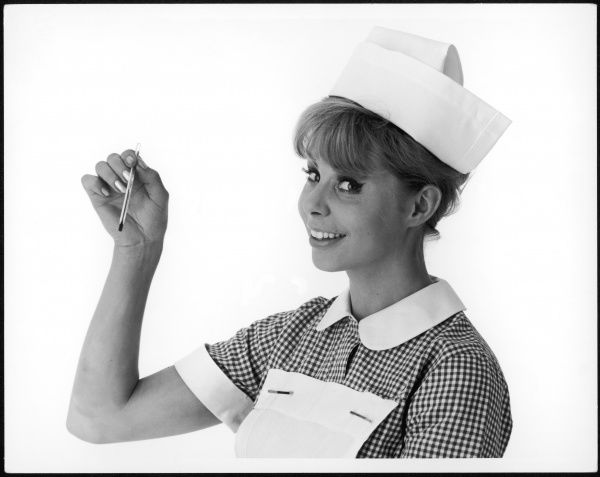 A smiling nurse brandishing a thermometer!