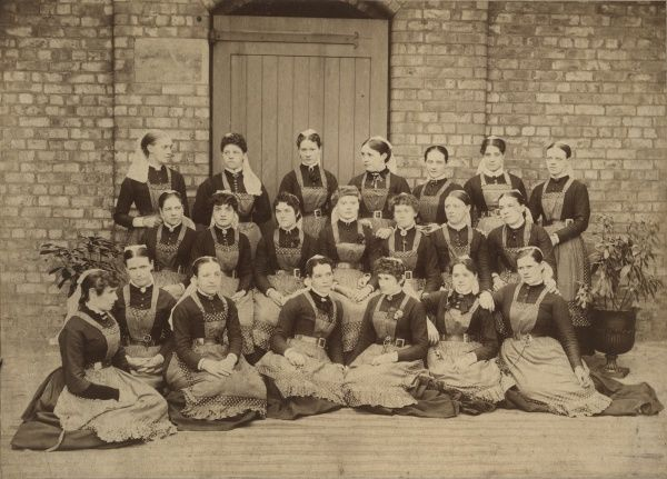 A group of uniformed women, thought to be nurses at the Chorlton Union workhouse in Withington near Manchester. Each is wearing a leather belt with keys attached. Date: Date unknown