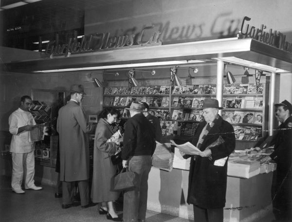 Men and women browse through an array of newspapers and magazines on sale at the Garfield News Company stand at New York port authority bus terminal