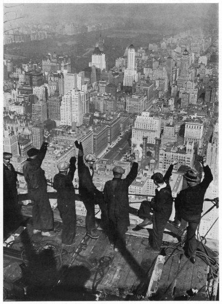 Building workers wave to the city below them