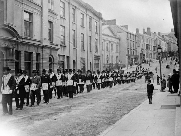 Members of the Independent Order of Odd Fellows, a masonic-style friendly society, make their way in costume along Victoria Place in Haverfordwest, Pembrokeshire, Dyfed, South Wales
