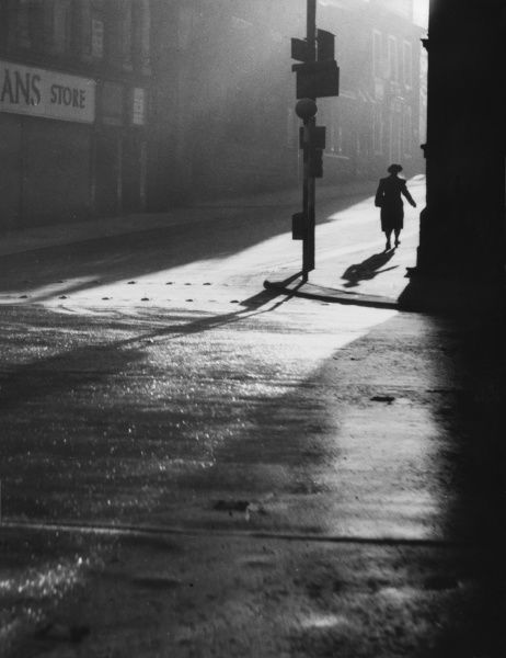 A woman goes off to work in the early morning sunshine, at atmospheric scene in Church Street, Blackburn, Lanacashire, England