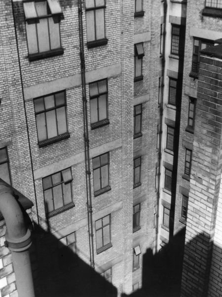 'Looking down the Well' - an angle photograph of office buildings. Date: 1930s