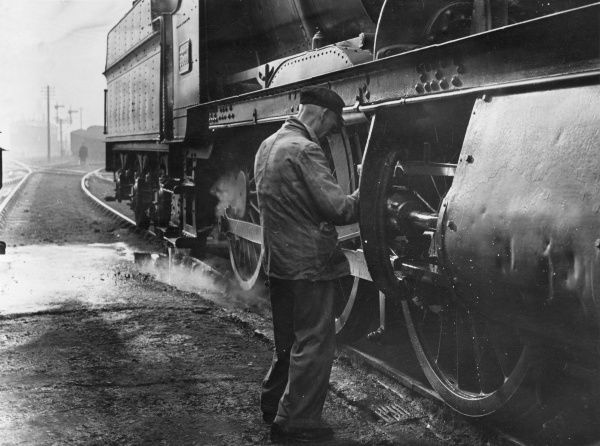 A maintenance worker oiling up the pistons of a steam locomotive