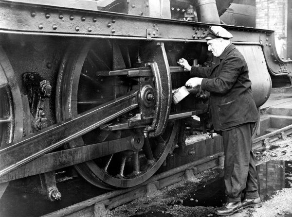 A railway maintenance worker oiling up the pistons of a steam locomotive. Date: 1957