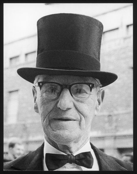 An elderly man wearing a top hat, spectacles and bow tie