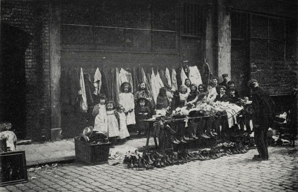 An old clothes stall in the East End of London. A crowd of children stand behind the stall, whose offerings include shoes, boots and a boxful of hats