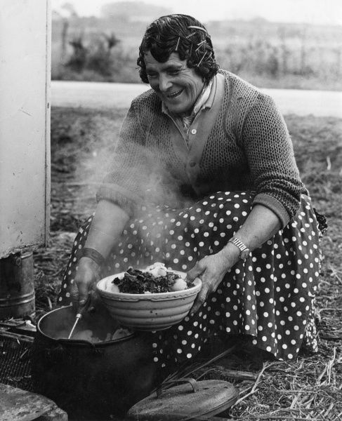 An old gipsy woman grins as she serves up potatoes and cabbage (?) from a boiling cauldron