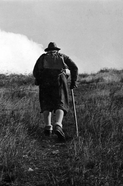 An old man takes to the hills for a healthy hike! Date: 1930s