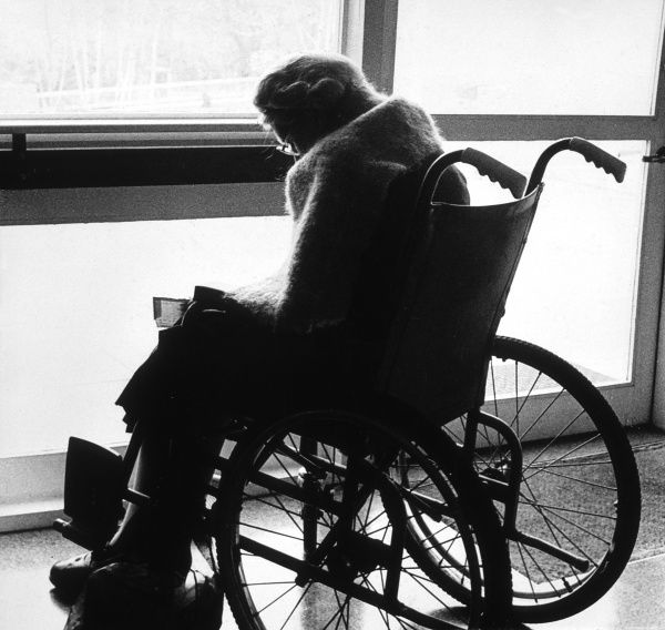 An old lady in her wheelchair by a window Date: circa 1960