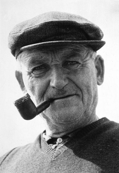 A characterful old man wearing a flat cap smokes his pipe. Date: 1950s
