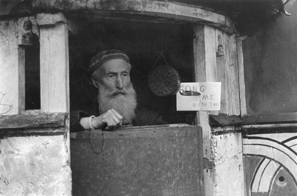 "This photograph is reminiscent of the Edward Lear nonsense poem. An old man with a long beard sits inside a small hut with a gong hanging from the door. Alongside is a written instruction or request, ""Gong Me With This&quot"