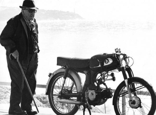 An old man with a walking stick, standing next to a motorcycle parked near a beach