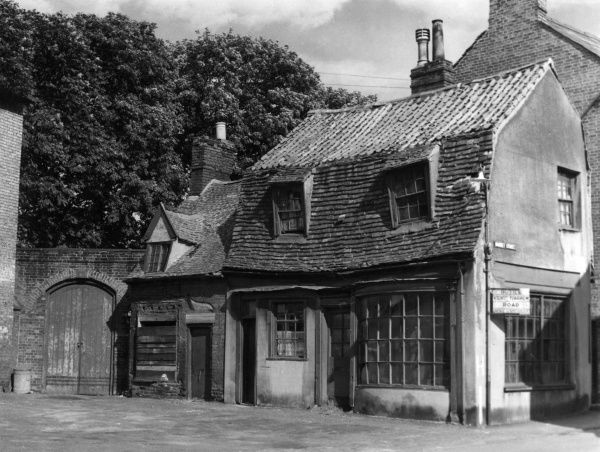 An interesting old 'crooked' shop, which is definately 'ripe for renovation', Newmarket, Suffolk, England. Date: 1960s