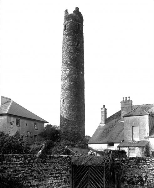 An old round tower somewhere in Devon, with houses surrounding it. Photograph by Ralph Ponsonby Watts