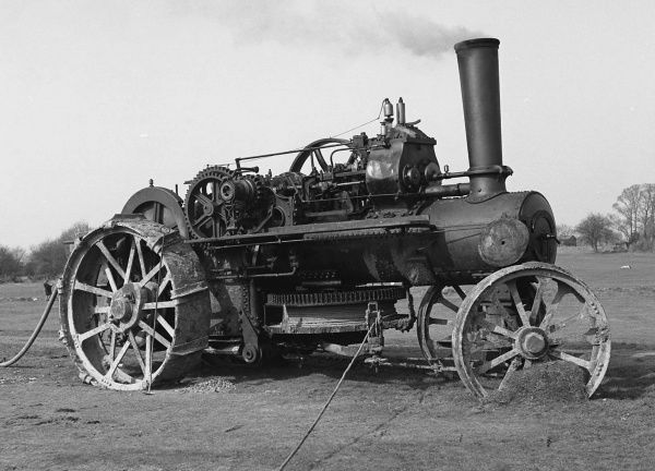 An old steam engine, puffing away in a field, still in use for something or other