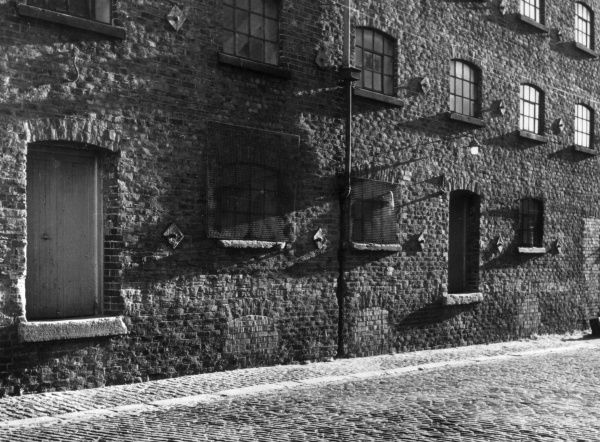 The sun catches the front of some old warehouses, Britain. Date: 19th century