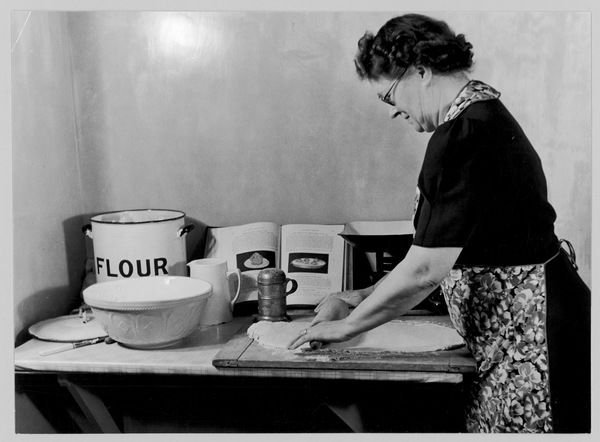 An older woman wearing a flowery apron rolls out pastry for some home baking