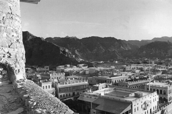 The white palaces of Muscat, Oman, are closed in on three sides by the black mountains. Their jagged cliffs hold in the warmth of the sun, making Muscat unbearably hot. Date: 1930s