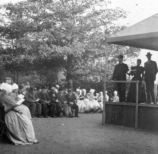 An open air church service for workhouse inmates, location unknown. Male and female inmates in workhouse uniform sit on chairs while a service is conducted by two men and a woman in formal dress on an elevated platform