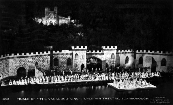 A night-time production of The Vagabond King at the open air theatre in Scarborough, North Yorkshire. The full cast appears to be on stage for the Finale, and some are on a floating platform on the water. Date: 1950