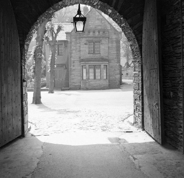 An open gateway with a fine gas lamp hanging at the point of the arch and two large wooden doors both opened fully. The open portal reveals a view though to an attractive small stone house in the sunshine. Photograph by Norman Synge Waller Budd