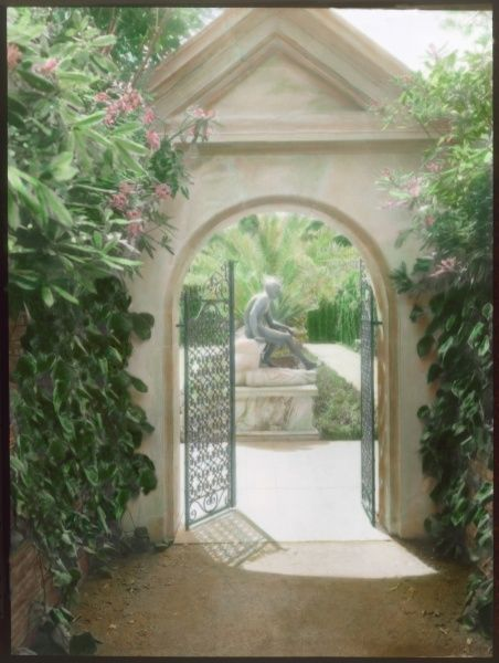 An open gateway into an Italian garden. The statue of a boy is framed inside the archway