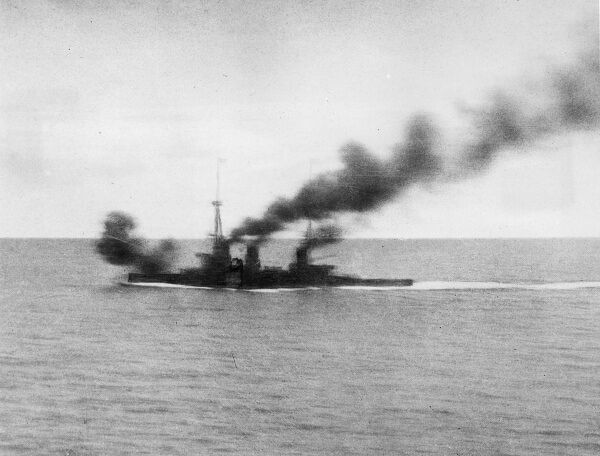 HMS Inflexible opening fire at the enemy at about 1pm, beginning the Battle of the Falkland Islands during the First World War. Photo taken from the maintop of HMS Invincible by Sub-Lieutenant Duckworth. Date: 8 December 1914