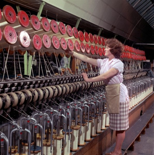 A woman operating and checking a huge wool winding machine at Patons & Baldwins factory at Darlington. Patons & Baldwins was one of the largest manufacturers of knitting yarn in the UK between the 1970 and the 1980s. Photograph by Heinz Zinram