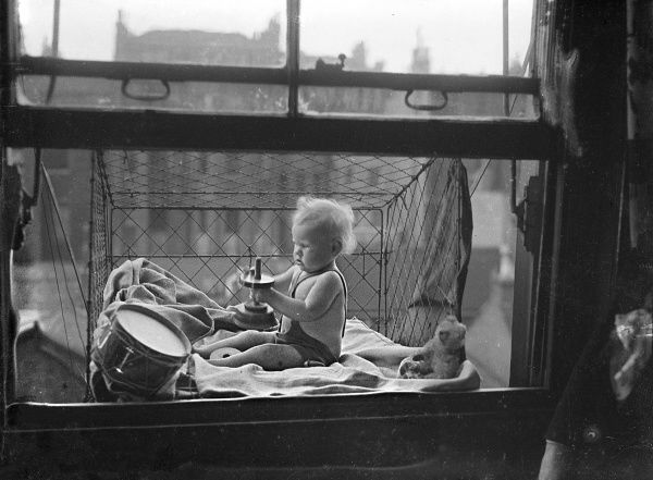 A handy baby cage, which can easily be fitted outside the window of even a modest flat. The mother can relax indoors while the baby plays with its toys in the fresh air... Date: 1930s