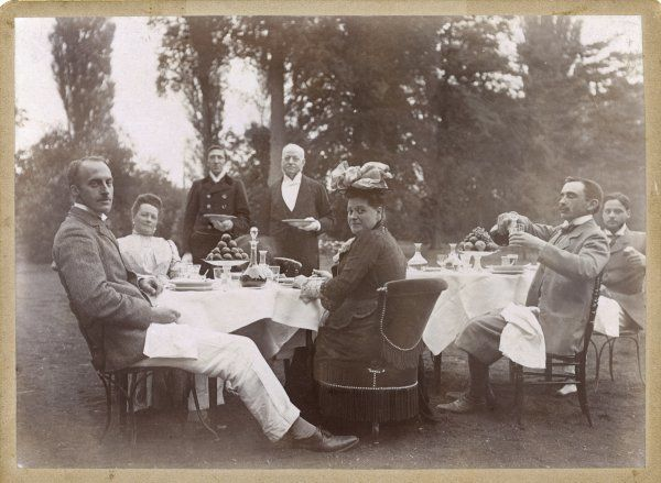 An upper class French group take dinner and drinks outdoors, waited upon by their servants
