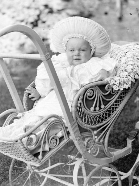An overdressed baby in an ornate pram, in a garden in Mid Wales