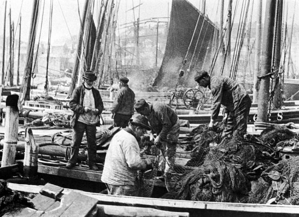 Fishermen overhaul the nets on their boats at Scarborough, Yorkshire