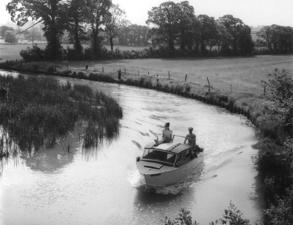 A young couple in a motor cruiser, rounding a bend on the Oxford Canal, near Lower Shuckburgh, Warwickshire, England. Date: early 1960s