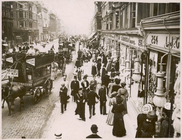 A busy scene in Oxford Street, London with many pedestrians on the pavements and horse- buses on the cobbled street