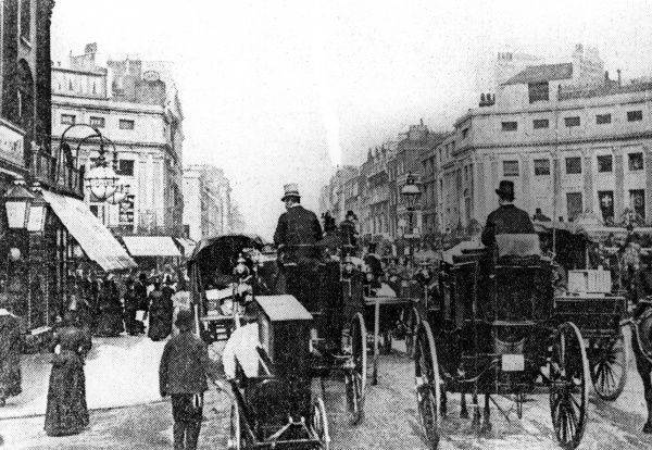 Horse-drawn traffic - and an organ grinder - near Oxford Circus. Date: 1890s