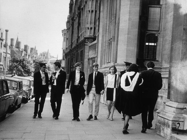 A group of students, male and female, walking down the street. Date: 1950s