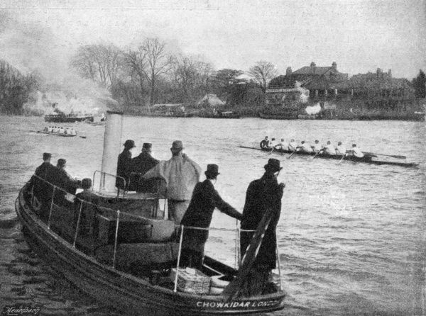 Spectators on board a boat watch as the university boat race teams head towards the finish at Mortlake. Oxford won this race, for the sixth year in succession