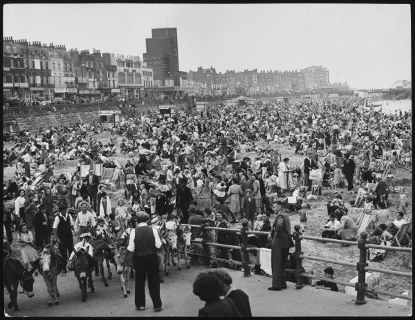 A very crowded beach scene at Margate, packed with British families enjoying the sun on deckchairs and donkeys, with the delights of Dreamland in the background