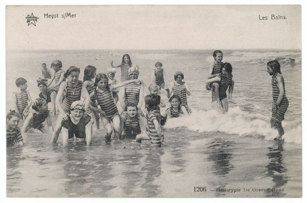 A group of children in striped bathing costumes paddle happily in the surf at Heyst sur Mer, Belgium