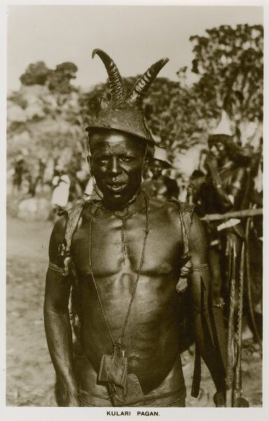 A 'Pagan' man from the Kulara region in Eastern Nigeria, wearing a splendid horned hat and a talismanic pouch around his neck containing charms