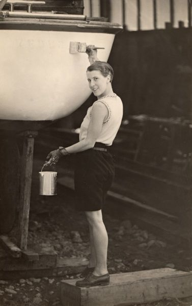 A woman wearing shorts and a sleeveless top poses rather coquettishly with a brush and paint tin as she gives her boat, standing in dry dock, a lick of paint