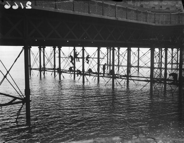 Men painting one of Brighton's piers, England