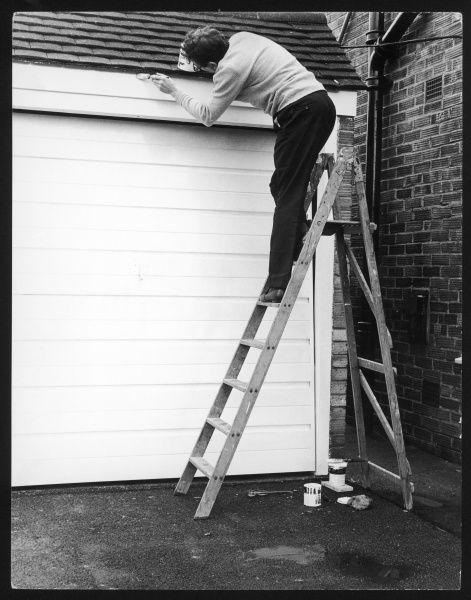 A house-proud British man, up a step ladder, painting the door and surrounds of his garage
