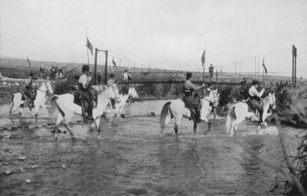 A Palestine gendarmerie cavalry patrol fording the river Hisbani near Khasas; emergency suspension bridge being completed to assist in evacuation during floods