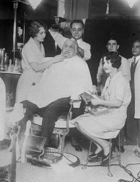 This poor old man is having his hair cut, beard shaved and a manicure, simultaneously! Date: 1930s