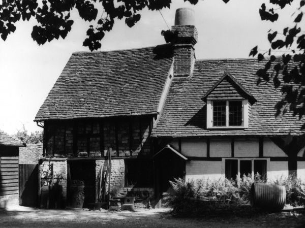 The lovely old smithy (blacksmiths) at Pangbourne, Berkshire, England. Note the nice fat chimney! Date: 1930s