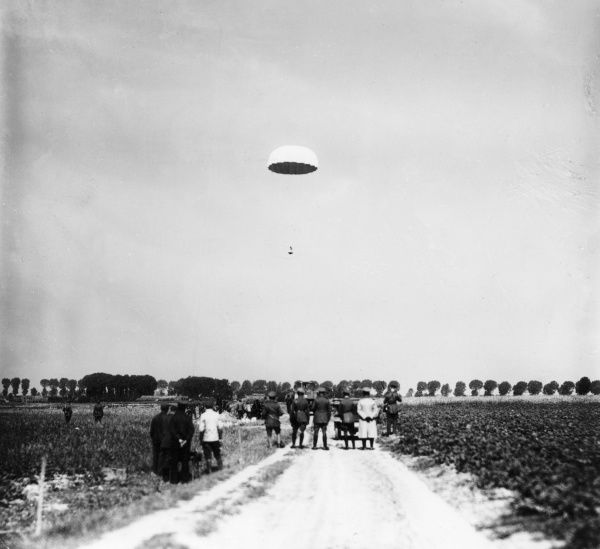A parachute descending at Fournes, northern France, during the First World War, watched by officers (probably German) on the ground. Date: August 1917